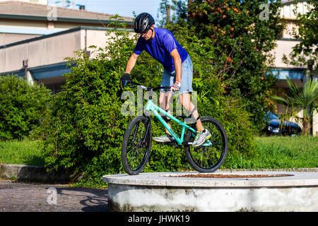 Cyclist on a mountain bike standing on a stone decoration. - Stock Image