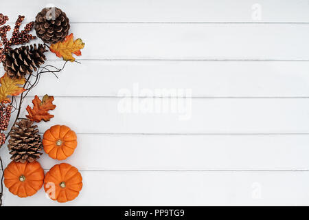 Rustic fall background of autumn leaves, pine cones and mini pumpkins with free copy space for text over a white rustic background. - Stock Image
