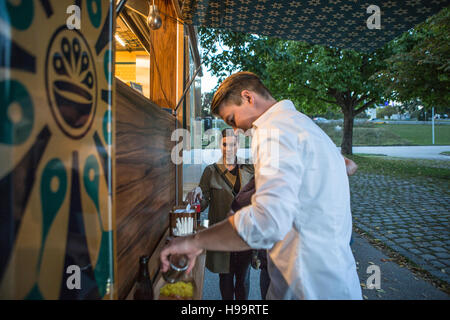 Male customer eating dish at food truck - Stock Image