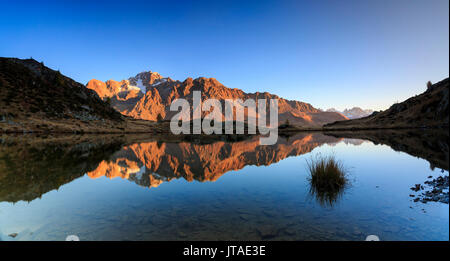 Panorama of the rocky peaks of Mount Disgrazia reflected in Lake Zana at dawn, Malenco Valley, Valtellina, Lombardy, Italy - Stock Image