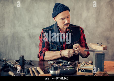 ambitious guy cleaning, repairing, and fabricating jewelry.close up photo - Stock Image
