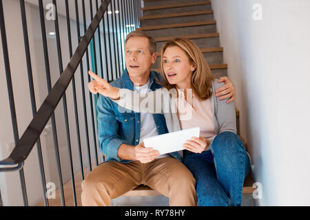 woman pointing with finger while sitting on stairs with husband and using digital tablet - Stock Image