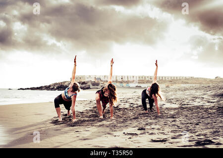 Pilates balance position three young active women at the beach doing sport fitness activity together under a dramatic cloudy sky - scenic image of peo - Stock Image