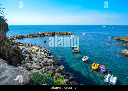 Boats and rafts moored in a small harbour near Riomaggiore, Cinque Terre Italy on a sunny day with blue sky, tourists - Stock Image