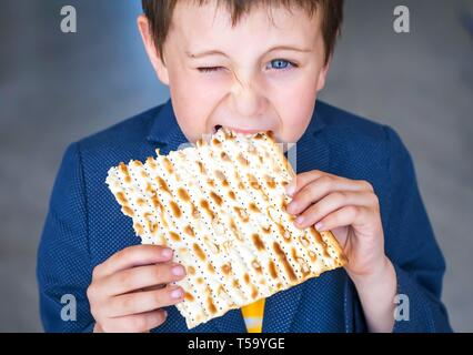 Cute Caucasian Jewish boy taking a bite from a traditional Jewish matzo unleavened bread. Jewish Passover Pesach concept image. Pesach child stock - Stock Image
