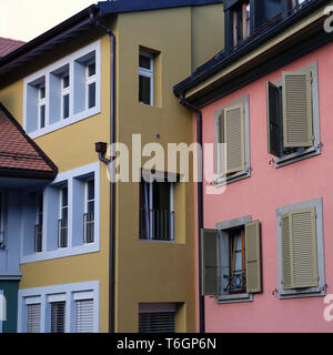 Colorful walls of Nyon, Switzerland. March 2019. In this photo you can see pink, yellow and blue walls with a lot of medieval style windows. - Stock Image