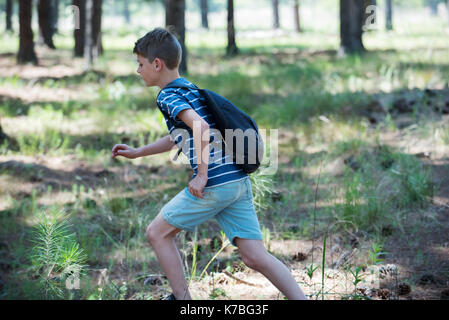 Boy running outdoors - Stock Image