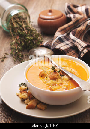 pumpkin soup - puree with croutons  in a white bowl on the old wooden background - Stock Image