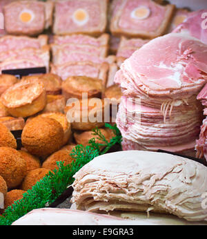 Sliced meats and a selection of various local products on display in the meat counter at a butchers or delicatessen - Stock Image