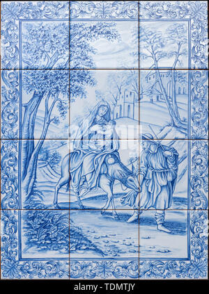 CATANIA, ITALY - APRIL 8, 2018: The ceramic tiled Flight to Egypt scene on the facade of Curia Arcivescovile by F. Fodinlio from 20. cent. - Stock Image