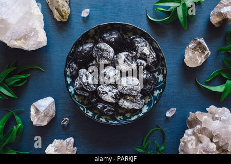 Apache Tears and Quartz on Blue Table - Stock Image