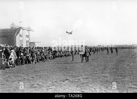 A biplane flying over an airfield. Left in the picture is an airship hall. - Stock Image