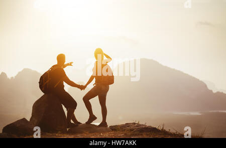 Couple backpackers on mountain top at sunset - Stock Image