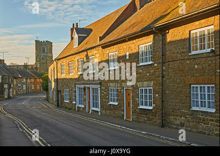 Street scene in the small Dorset village of Abbotsbury with the road leading towards the small church of St Nicholas. - Stock Image