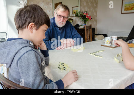 A young boy plays a game of dominoes with his grandfather on a dining room table. - Stock Image