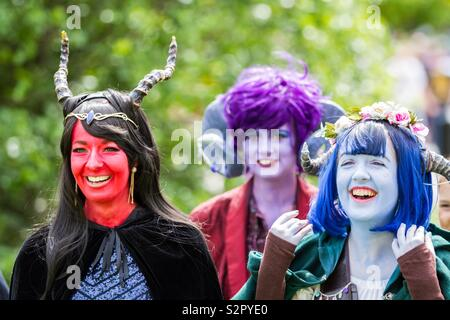 A group of cosplay girls dressed as critters with colourful face paint and wigs laughing together in a candid portrait at a comic con event - Stock Image