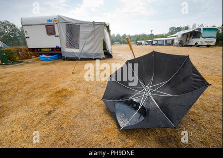 HAAKSBERGEN, THE NETHERLANDS - AUG 09, 2018: An umbrella is lying upside down on the ground after a downpour on a dutch camping in the summer. - Stock Image