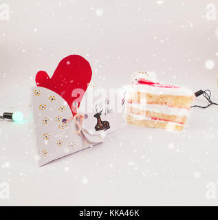 Christmas Decoration with Gifts and Cake  under snow with lights for best background image for Holiday greeting - Stock Image