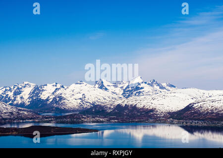 Snow capped mountains reflected in fjord sea around Tromsoya Island in summer. Tromso, Troms, Norway, Scandinavia, Europe - Stock Image