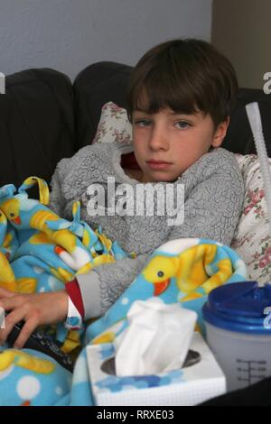 Sick child on couch watching television - Stock Image