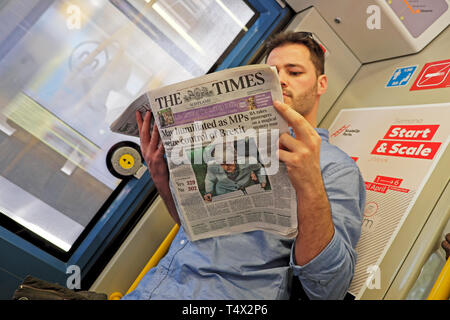 Man reading British paper in Europe 'May humiliated as MPs seize control of Brexit' Times newspaper headline 26 March 2019 Porto Portugal KATHY DEWITT - Stock Image