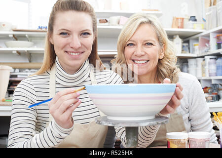 Portrait Of Woman Decorating Bowl With Teacher In Pottery Class - Stock Image