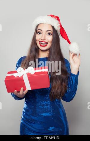 Beautiful Santa woman in braces holding Christmas gift - Stock Image
