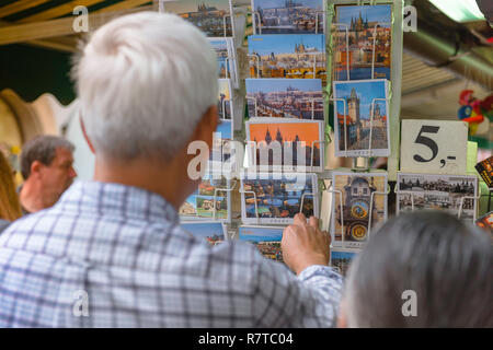 Prague tourism, rear view of a tourist in the Havelske Market in Prague browsing postcards showing the city's iconic imagery, Czech Republic. - Stock Image