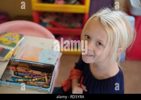 A 5 year old blond Caucasian girl grips a crayon while coloring, and smiles up at the camera. USA. - Stock Image