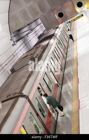 Train subway seen from above with conductor walking to front and passenger boarding - Stock Image
