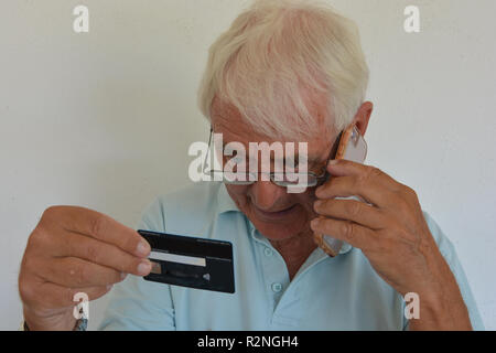 Senior man giving his credit card details over phone, talking and looking concerned. - Stock Image