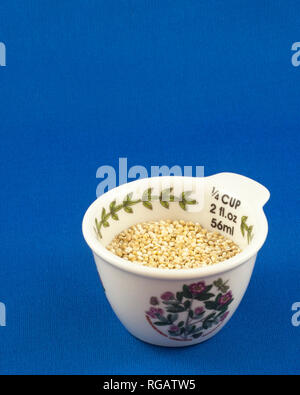 Measuring cup filled with 1/4 cup of organic golden (white) quinoa (Chenopodium quinoa) - Stock Image