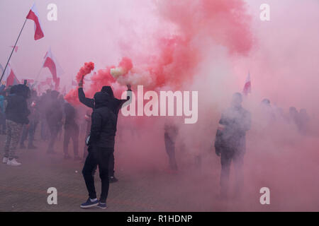 Warsaw, Poland, 11 November 2018: Man with red and white smoking flare - Stock Image