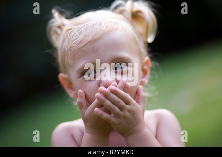A two-year-old girl with pig tails acts surprised while playing outdooors. - Stock Image