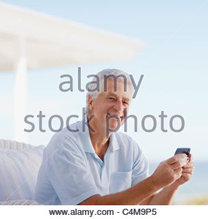 Senior man holding cell phone on patio - Stock Image