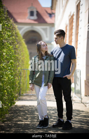 A young couple traveling. Standing on the street and look at each other. Mid shot - Stock Image