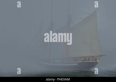 Two masted Schooner with sails on port-side tack sails into dense fog - Stock Image