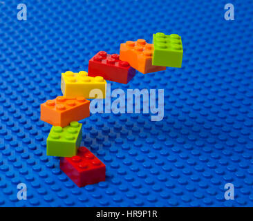 Upward spiral construction or staircase of interlocking Lego bricks on a blue Lego base plate. - Stock Image