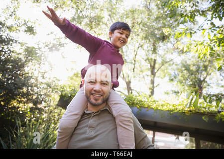 Portrait playful father carrying son on shoulders in park - Stock Image