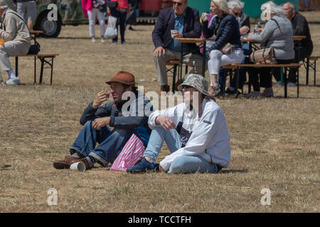two men sat on the grass in bucket hats at an outdoor event or festival - Stock Image