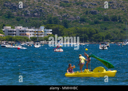 Children on a yellow pedalo in the waters of Port de Pollenca in Mallorca, Spain - Stock Image