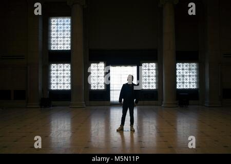 A man stands in the middle of the ballroom at the Asian Art Museum in San Francisco. - Stock Image