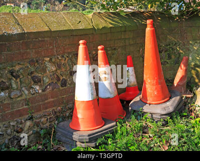 Road safety cones stored behind a wall in the countryside at Wickhampton, Norfolk, England, United Kingdom, Europe. - Stock Image