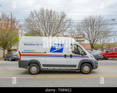 New modern U.S. Postal Service delivery van or mail truck parked on a city street making deliveries in downtown Montgomery Alabama, USA. - Stock Image