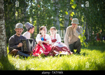 People in traditional Russian clothes sit on the lawn and talk - one of them plays the accordion and smile - gorizontal view - Stock Image