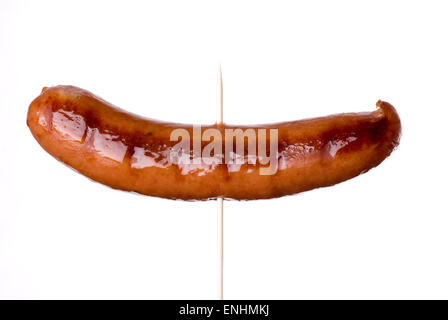 Grilled sausage on a skewer close up. - Stock Image