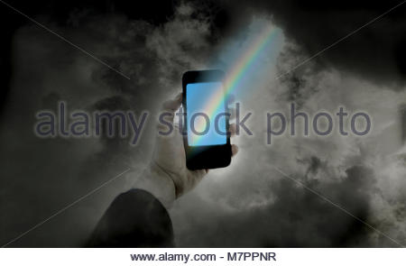 The end of a rainbow on a smart phone in man's hand - Stock Image