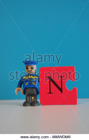 Mail man toy figure holding a red puzzle part with the letter N - Stock Image