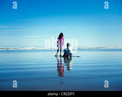 Girl watches boy build sandcastle on beach - Stock Image