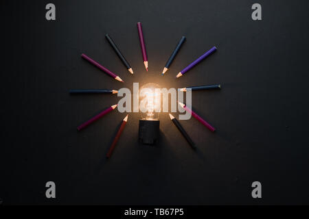 Light bulb shining in black on black flat lay with pencils. The idea for engineering, building or construction concept with copy space. - Stock Image